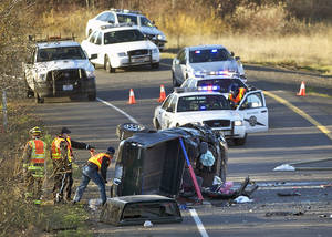 Photo - In this Dec. 4, 2013 photo, crews respond to an accident in Vancouver, Wash. Caran Johnson who regularly monitors police scanner traffic unknowingly live-tweeted about her husband's death in the freeway crash. (AP Photo/The Columbian, Zachary Kaufman)