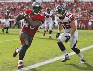 Photo - Tampa Bay Buccaneers running back Bobby Rainey (43) scores past Atlanta Falcons outside linebacker Paul Worrilow (55) on a 4-yard touchdown reception during the third quarter of an NFL football game on Sunday, Nov. 17, 2013, in Tampa, Fla. (AP Photo/Reinhold Matay)