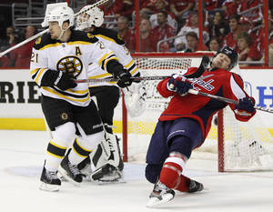 Photo -   Boston Bruins defenseman Andrew Ference (21) knocks down Washington Capitals left wing Matt Hendricks (26) as \Bruins goalie Tim Thomas looks up the ice during the second period of Game 4 in a first-round NHL Stanley Cup playoff hockey series, Thursday, April 19, 2012, in Washington. (AP Photo/Evan Vucci)