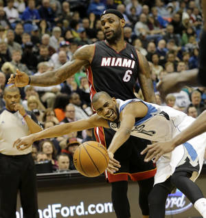 Photo - Minnesota Timberwolves forward Corey Brewer (13) loses control of the ball after colliding with Miami Heat forward LeBron James (6) during the third quarter of an NBA basketball game in Minneapolis, Saturday, Dec. 7, 2013. The Heat won 103-82. (AP Photo/Ann Heisenfelt)