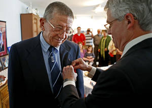 photo - Retired Maj. Gen. Stanley Newman receives the Medal of Chevalier of the French National Order of the Legion of Honor from Grant Moak, Honorary French Consul for Oklahoma, as friends and family watch inside his daughter's Oklahoma City home, Saturday, March 16, 2013. Photo by Bryan Terry, The Oklahoman