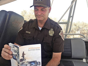 Photo - Oklahoma Highway Patrol trooper George Hoyle reads over the manual to the new sonar equipment that was used to find two cars that were submerged in Foss Lake for more than 40 years. <strong>Juliana Keeping</strong>