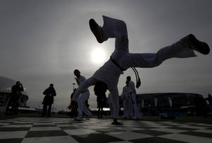 Photo - Street performers dance capoeira as a crowd watches in Olympic Park during the 2014 Winter Olympics, Sunday, Feb. 9, 2014, in Sochi, Russia. (AP Photo/Julio Cortez)