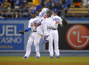 Photo - Los Angeles Dodgers' Yasiel Puig, center, celebrates with Carl Crawford, left, and Skip Schumaker after they defeated the New York Mets 4-2 in their baseball game, Tuesday, Aug. 13, 2013, in Los Angeles. (AP Photo/Mark J. Terrill)