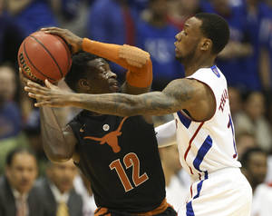 Photo - Texas guard Myck Kabongo (12) looks to pass around Kansas uard Naadir Tharpe during the first half of an NCAA college basketball game on Saturday, Feb. 16, 2013, in Lawrence, Kan. (AP Photo/Ed Zurga)