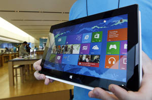photo -   A Microsoft store product advisor displays the new Surface table computer as customers enter the store as it opens Friday, Oct. 26, 2012 in Seattle. Friday was the first day of sales for the new Windows 8 operating system and the company's new tablet computer, the Surface. (AP Photo/Elaine Thompson)