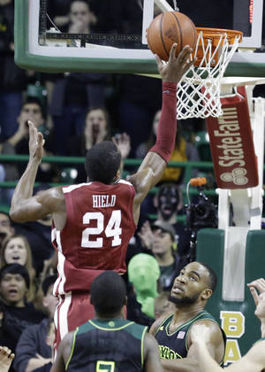 Photo - Buddy Hield (24) scores over Baylor forward Rico Gathers (2) during the second half of an NCAA college basketball game Saturday, Jan. 18, 2014, in Waco, Texas. Oklahoma won 66-64. (AP Photo/LM Otero)