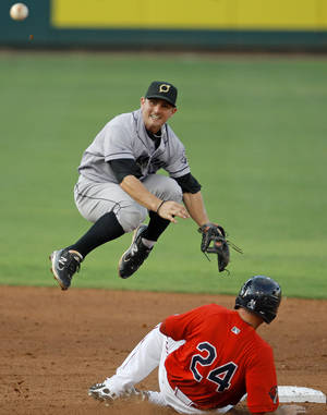 photo - Johnny Giavotella of the Omaha Storm Chasers leaps over Drew Locke of the Oklahoma City RedHawks to make the throw for a double play in the second inning of the baseball game at RedHawks Field at Bricktown in Oklahoma City, Friday, July 8, 2011. Photo by Bryan Terry, The Oklahoman ORG XMIT: KOD
