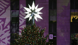 Photo - The Swarovski star shines atop the Rockefeller Center Christmas tree after it was lit during a ceremony, Wednesday, Dec. 4, 2013, in New York. Some 45,000 energy efficient LED lights adorn the 76-foot tree. (AP Photo/Kathy Willens)