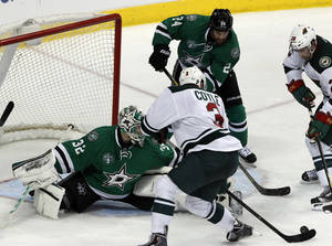 Photo - Dallas Stars goalie Kari Lehtonen (32) defends as Minnesota Wild center Charlie Coyle (3) goes to take a shot during the second period of an NHL hockey game in Dallas on Saturday, March 8, 2014.(AP Photo/ Richard W. Rodriguez)
