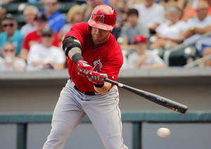 Photo - Los Angeles Angels' Josh Hamilton swings against the Chicago Cubs' during the first inning of a spring training baseball game, Tuesday, March 25, 2014, in Mesa, Ariz. (AP Photo/Matt York)