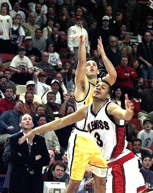 photo - FILE-- Valparaiso college basketball player Bryce Drew (20) follows through with his game-winning three-point shot at the buzzer against Mississippi's Jason Flanigan (3) in their first round game of the NCAA Midwest Regional tournament in this March 13, 1998  photo, in Oklahoma City. At left is Valparaiso coach Homer Drew watches his son's shot. Let the argument begin: Was this the best tournament ever? Drew's buzzer beater was one of many memorable moments in the 1998 NCAA tournament. (AP Photo/J.Pat Carter)