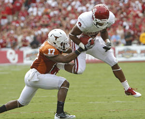 Photo - Oklahoma's Dominique Whaley (8) runs past Texas' Adrian Phillips (17) during the Red River Rivalry college football game between the University of Oklahoma Sooners (OU) and the University of Texas Longhorns (UT) at the Cotton Bowl in Dallas, Saturday, Oct. 8, 2011. Photo by Chris Landsberger, The Oklahoman