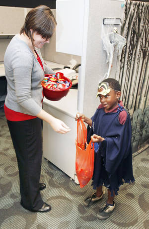 "Photo - ""Tyler"" receives candy from Brieanne Nguyen as Positive Tomorrows kids trick or treat through the offices of the Oklahoma Medical Research Foundation. Paul Hellstern, The Oklahoman <strong>PAUL HELLSTERN - Oklahoman</strong>"