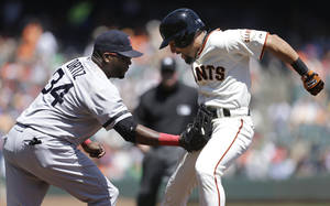 Photo - Boston Red Sox first baseman David Ortiz (34) tags out San Francisco Giants' Andres Torres while Torres was caught trying to steal second base during the first inning of a baseball game in San Francisco, Wednesday, Aug. 21, 2013. (AP Photo/Jeff Chiu)