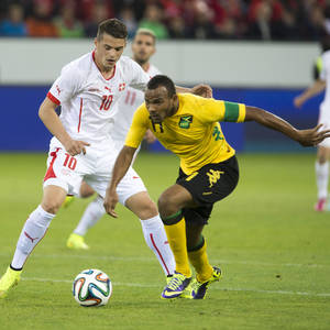 Photo - Xherdan Shaqiri of Switzerland, left, and Rodolph Austin of Jamaika fight for the ball, during the international friendly soccer match between Switzerland and Jamaica at the swissporarena in Lucerne, Switzerland, Friday, May 30, 2014. Switzerland are preparing for the upcoming FIFA soccer World Cup in Brazil starting on 12 June. (AP Photo/Keystone, Sigi Tischler)