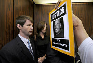 Photo - FILE- In this Nov. 17, 2011 file photo, an unidentified protester shoves a sign in the face of State Department Special Agent Christopher Deedy, left, and his wife on an elevator in Honolulu. Deedy, of Arlington, Va., is back in Honolulu to stand trial a second time for killing Kollin Elderts during an altercation in a McDonald's restaurant. He contends the shooting was self-defense. Free on $250,000, bail, he returned home after the first trial. (AP Photo/Honolulu Star Advertiser, Dennis Oda, File)