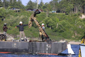 Photo - Work crews pull out an anchor from Admiralty Inlet off Whidbey Island, Wash., on Monday, June 9, 2014.  The anchor was found six years ago by sea-cucumber diver Doug Monk who formed Anchor Ventures with amateur historian Scott Grimm to bring it to the surface.  The anchor may be the anchor lost by the HMS Chatham as it explored with Capt. George Vancouver's HMS Discovery in 1792. The 900-pound anchor was taken Monday to the Northwest Maritime Center in Port Townsend.    (AP Photo/The Seattle Times, Steve Ringman)  SEATTLE OUT; USA TODAY OUT; MAGS OUT; TELEVISION OUT; NO SALES; MANDATORY CREDIT TO BOTH THE SEATTLE TIMES AND THE PHOTOGRAPHER