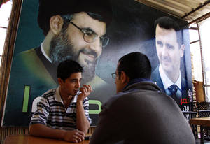 Photo - FILE - In this May 9, 2009 file photo, two Syrian men sit at a coffee shop under a big poster showing Syrian President Bashar Assad, right, and Hezbollah leader Sheik Hassan Nassrallah, left, in Damascus, Syria. U.S. officials said Israel launched a rare airstrike inside Syria on Wednesday. The target was a convoy believed to be carrying anti-aircraft weapons bound for Hezbollah, the powerful Lebanese militant group allied with Syria and Iran. The Israeli airstrike comes at a particularly sensitive and vulnerable time for Hezbollah in Lebanon. Despite its formidable weapons arsenal and political clout in the country, the group's credibility and maneuvering space has been significantly reduced in the past few years, largely because of the war in neighboring Syria but also because of unprecedented challenges at home. (AP Photo/Ola Rifai, File)
