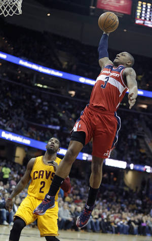 Photo - Washington Wizards' Bradley Beal (3) dunks over Cleveland Cavaliers' Kyrie Irving (2) in the first quarter of an NBA basketball game, Sunday, Feb. 23, 2014, in Cleveland. (AP Photo/Mark Duncan)