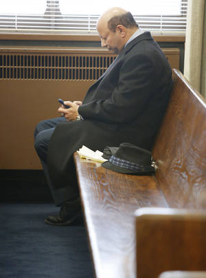 Photo - Dr. Medhat Michael waits for his hearing to start at the Oklahoma County Courthouse in Oklahoma City on Wednesday. PHOTO BY STEVE GOOCH, THE OKLAHOMAN <strong>Steve Gooch</strong>