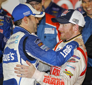 Photo - Dale Earnhardt Jr., right, celebrates in Victory Lane with teammate Jimmie Johnson, left, after winning the NASCAR Daytona 500 Sprint Cup series auto race at Daytona International Speedway in Daytona Beach, Fla., Sunday, Feb. 23, 2014. (AP Photo/Terry Renna)
