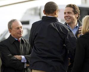 Photo - <p>FILE - In this Nov. 15, 2012 file photo, President Barack Obama, center, is flanked by New York City Mayor Michael Bloomberg, left, and New York Gov. Andrew Cuomo, after the president arrived at John F. Kennedy International Airport in New York, to visit areas devastated by Superstorm Sandy. Experts in leadership and disaster response give Bloomberg, Cuomo and New Jersey Gov. Chris Christie high marks for their performance so far in Superstorm Sandy, a disaster that left more than 100 people dead and presented perhaps the biggest crisis-management test yet for the three Northeastern politicians who have all been rumored to hold presidential ambitions. (AP Photo/Carolyn Kaster, File)</p>