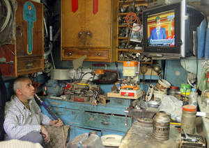 "photo - An Egyptian key maker smokes a water pipe as he watches President Mohammed Morsi speaks at the Shura Council, the country's upper house of parliament, in Cairo, Saturday, Dec. 29, 2012. Egypt's Islamist president has warned against any unrest that could harm the drive to repair the country's economy in a sharply worded speech pushing the opposition to work with his government. Mohammed Morsi has made the comments in his first speech to the newly convened upper house of parliament, saying it was time for the nation to turn to ""production, work, seriousness"" after two years of turmoil. (AP Photo/Amr Nabil)"