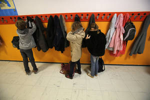 Photo -   Students hang their jackets as they arrive at the school of La Ronce in Ville d'Avray, west of Paris, Friday, Oct. 5, 2012. French children go to school four days a week with about two hours each day for lunch. And they have more vacation than their counterparts almost anywhere in the West. As a candidate, President Francois Hollande promised to change things by adding a fifth day of classes on Wednesday while shortening the school day and education minister, Vincent Peillon, will decide this month how to carry out the reform. (AP Photo/Christophe Ena)