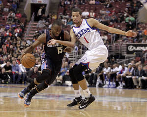 Photo - Charlotte Bobcats' Kemba Walker (15) drives against Philadelphia 76ers' Michael Carter-Williams (1) in the first half of an NBA basketball game, Wednesday, Jan. 15, 2014 in Philadelphia. (AP Photo/H. Rumph Jr.)