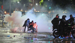 Photo - Soccer fans try to escape from a tear gas cloud and a police water cannon, used to restrain a group of youths who hurled rocks and vandalized stores, at a rally after Argentina's performance in a 1-0 loss to Germany in the World Cup finals, Sunday, July 13, 2014, in Buenos Aires, Argentina. Police said more than a dozen officers were injured and many more were arrested. (AP Photo/Victor Carreira)