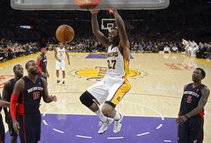 Photo - Los Angeles Lakers center Jordan Hill (27) dunks as Detroit Pistons forward Greg Monroe (10) and guard Kentavious Caldwell-Pope (5) look on during the second half of an NBA basketball game, Sunday, Nov. 17, 2013, in Los Angeles.  (AP Photo/Mark J. Terrill)