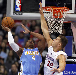 Photo - Denver Nuggets guard Randy Foye (4) shoots with Los Angeles Clippers forward Blake Griffin (32) defending during the first half of an NBA basketball game in Los Angeles on Saturday, Dec. 21, 2013. (AP Photo/Alex Gallardo)