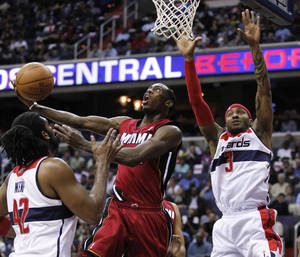 Photo -   Miami Heat guard Terrel Harris, center, drives to the basket against Washington Wizards defenders Nene, of Brazil, left, and James Singleton during the first half of an NBA basketball game on Thursday, April 26, 2012, in Washington. (AP Photo/Evan Vucci)