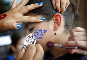 photo - Cielo Esparza gets her face painted during the grand reopening of Southern Oaks Library.