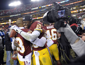 Photo - Washington Redskins cornerback DeAngelo Hall (23) celebrates with quarterback Robert Griffin III (10) after an NFL football game against the Dallas Cowboys on Sunday, Dec. 30, 2012, in Landover, Md. The Redskins won 28-18, securing a playoff berth. (AP Photo/Nick Wass)