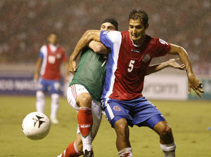 Photo - Costa Rica's Celso Borges, left, fights for the ball with Mexico's Christian Gimenez during a 2014 World Cup qualifying soccer match in San Jose, Costa Rica, Tuesday, Oct. 15, 2013. (AP Photo/Moises Castillo)