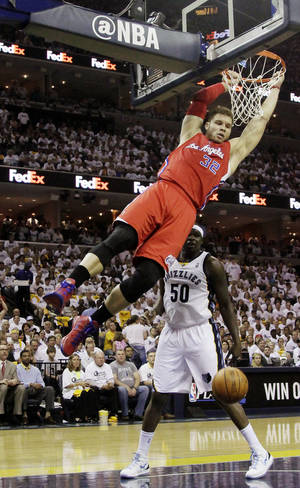 Photo -   Los Angeles Clippers' Blake Griffin (32) hangs on the basket after dunking over Memphis Grizzlies' Zach Randolph (50) during the first half in Game 1 of a first-round NBA basketball playoff series, Sunday, April 29, 2012, in Memphis, Tenn. (AP Photo/Danny Johnston)