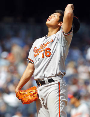 Photo -   Baltimore Orioles' pitcher Wei-Yin Chen (16) reacts after walking a batter against the New York Yankees in a baseball game Saturday, Sep. 1, 2012 at Yankee Stadium in New York. (AP Photo/Rich Schultz)
