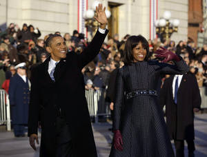 Photo - President Barack Obama and first lady Michelle Obama waves as they walk down Pennsylvania Avenue near the White House during the 57th Presidential Inauguration parade Monday, Jan. 21, 2013, in Washington. (AP Photo/Charles Dharapak)