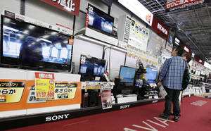 Photo - Customers visit a corner of Sony's Bravia flat-panel TVs at a Tokyo electronics store in Tokyo, Thursday, May 9, 2013. Sony Corp. is back in the black for the fiscal fourth quarter, recording a 93.9 billion yen ($948 million) profit, with big help from a weaker yen that boosts overseas earnings. (AP Photo/Koji Sasahara)