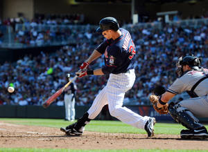 Photo -   Minnesota Twins' Justin Morneau, left, hits a two-run home run against Cleveland Indians pitcher Corey Kluber as catcher Lou Marson, right, looks on in the third inning of their baseball game in Minneapolis, Sunday, Sept. 9, 2012. (AP Photo/Craig Lassig)