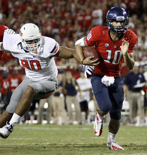 Photo -   Arizona quarterback Matt Scott (10) run for a touchdown pass Oklahoma defensive end Trace Clark (90) during the third quarter of an NCAA college football game at Arizona Stadium in Tucson, Ariz., Sat., Sept. 8, 2012. (AP Photo/Wily Low)