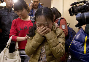 Photo - A Chinese relative of passengers aboard a missing Malaysia Airlines plane, center, cries as she is escorted by a woman while leaving a hotel room for relatives or friends of passengers aboard the missing airplane, in Beijing, China Sunday, March 9, 2014.  Planes and ships from across Asia resumed the hunt Sunday for the Malaysian jetliner missing with 239 people on board for more than 24 hours, while Malaysian aviation authorities investigated how two passengers were apparently able to get on the aircraft using stolen passports. (AP Photo/Andy Wong)