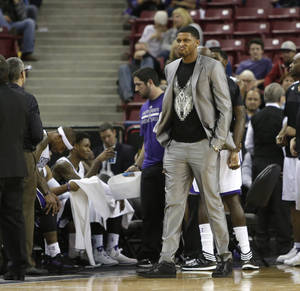 Photo - Sacramento Kings forward Rudy Gay grimaces as he walks on the court during a timeout in the closing moments of the Kings 125-117 loss to the Denver Nuggets in a NBA basketball game in Sacramento, Calif., Sunday, Jan. 26, 2014. Gay and Kings center DeMarcus Cousins did not suit up for the game due to injuries.(AP Photo/Rich Pedroncelli)