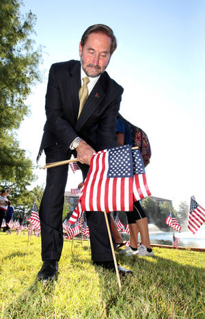Photo - UCO President Don Betz places an American flag near Broncho Lake during a ceremony to commemorate 9-11, Wednesday, September 11, 2013. Students, faculty and staff participated in the remembrance ceremony by placing 2,500 flags around Broncho Lake. Photo by David McDaniel, The Oklahoman