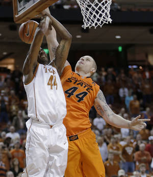 photo - Texas' Prince Ibeh, left, is blocked by Oklahoma State defender Philip Jurick, right,  as he tries to score during the first half of an NCAA college basketball game, Saturday, Feb. 9, 2013, in Austin, Texas. (AP Photo/Eric Gay)
