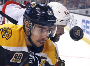 Photo - Boston Bruins center Chris Kelly, left, and Ottawa Senators defenseman Eric Gryba (62) battle for the puck along the boards during the second period of an NHL hockey game in Boston, Saturday, Feb. 8, 2014. (AP Photo/Elise Amendola)