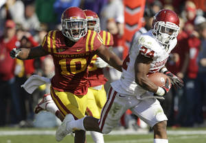 Photo -   Oklahoma running back Brennan Clay, right, runs from Iowa State defensive back Jacques Washington during an 18-yard touchdown run in the second half of an NCAA college football game, Saturday, Nov. 3, 2012, in Ames, Iowa. Oklahoma won 35-20. (AP Photo/Charlie Neibergall)