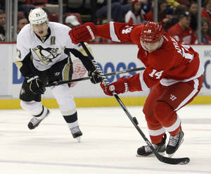 Photo - Detroit Red Wings' Gustav Nyquist (14), of Sweden, is pursued by Pittsburgh Penguins' Evgeni Malkin (71), of Russia, as he brings the puck down the ice during the second period of an NHL hockey game on Saturday, Dec. 14, 2013, in Detroit. (AP Photo/Duane Burleson)